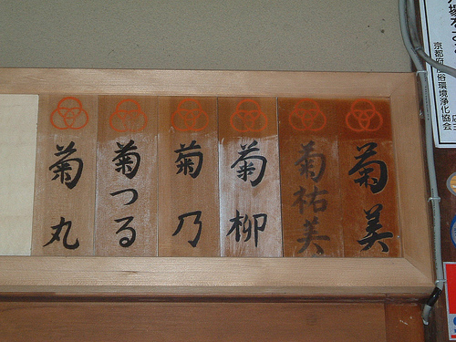 Tablillas a la entrada de una ochaya que muestran los nombres con kanjis compartidos de maikos y geishas (para demostrar que forman parte de una misma 'familia') Artículo publicado en Japonismo: La maiko o aprendiza de geisha http://japonismo.com/blog/la-maiko-o-aprendiza-de-geisha