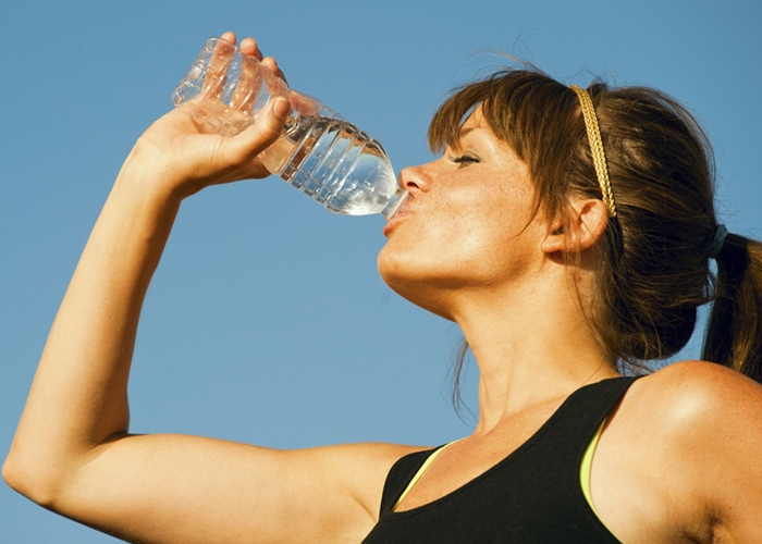 girl taking a drink / straight from a water bottle / in the great outdoors