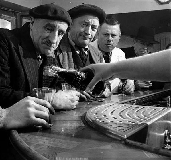 Grupo de hombres asombrados observan el lanzamiento de Coca Cola en Francia 1950