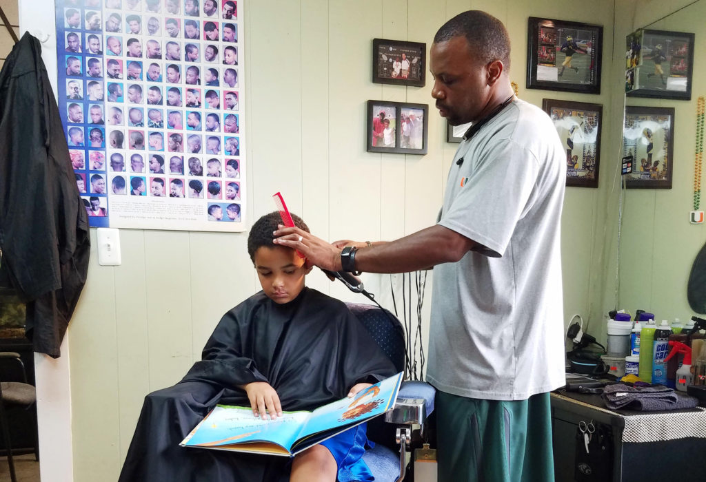Jozef Jason, 7, reads a book to Ryan Griffin at the Fuller Cut in Ypsilanti, Mich. as part of the barbershop's literacy program.
