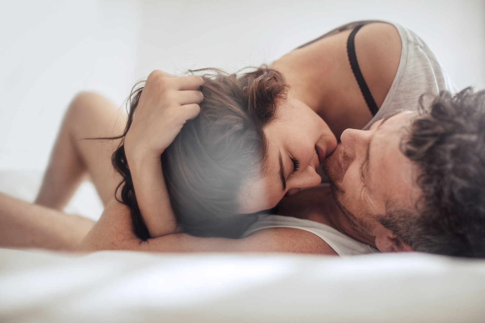 bigstock-Young-Couple-Caressing-In-Bed-163589933