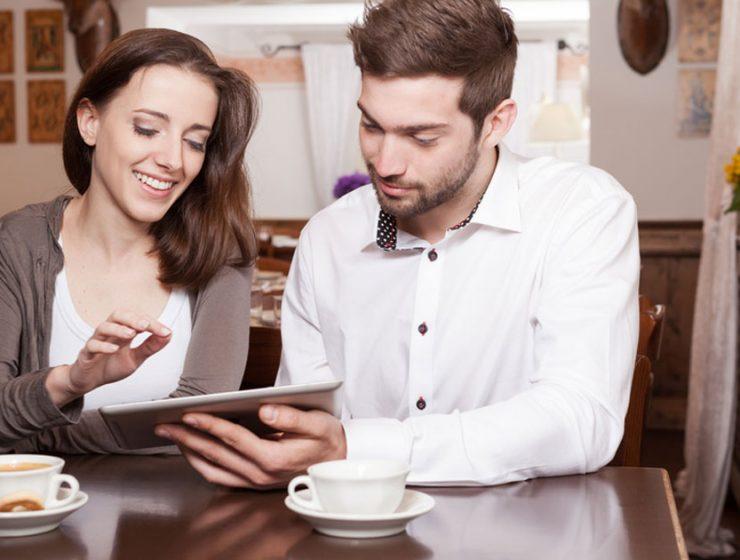 Pareja leyendo en una tablet en la cocina