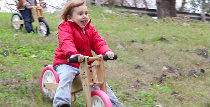 trikids - niña divertida con su bicicleta de aprendizaje,