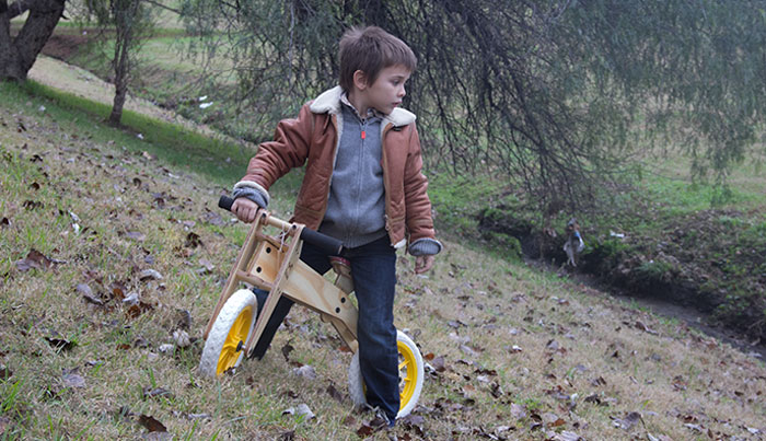 trikids - bicicleta de aprendizaje, niño en bici mirando hacia abajo