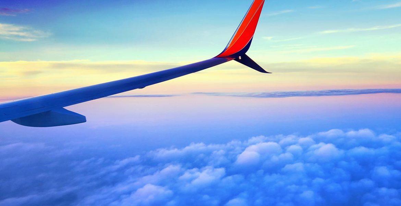 Avion volando sobre nubes - vista del ala desde la ventana
